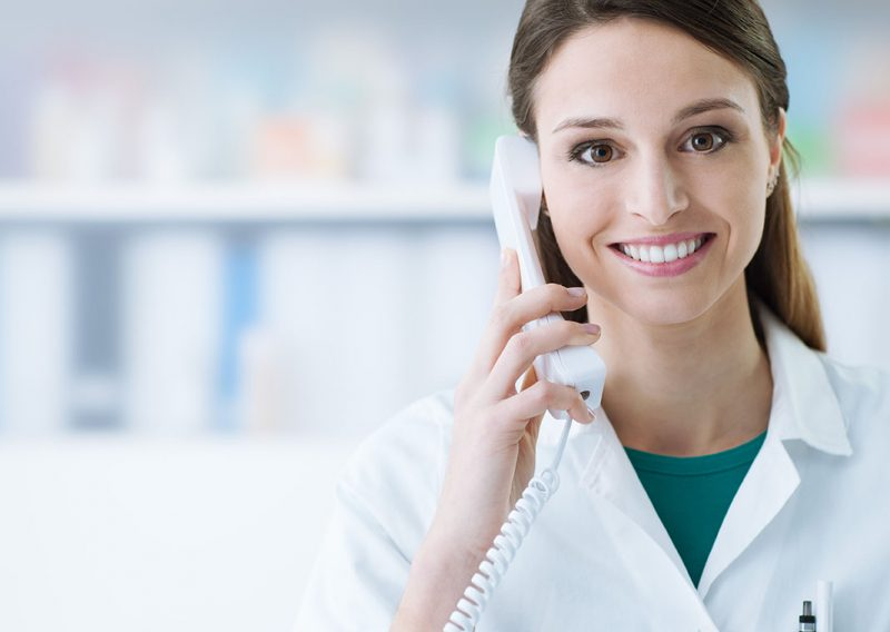 Smiling female doctor holding a receiver and answering phone calls, medical service