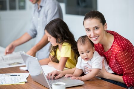 Portrait of smiling mother working on laptop with baby while daughter studying at desk